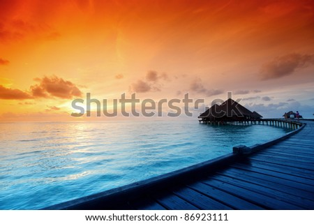 resort maldivian houses on sunrise - stock photo