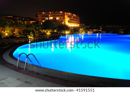 resort pool at night with blue illumination