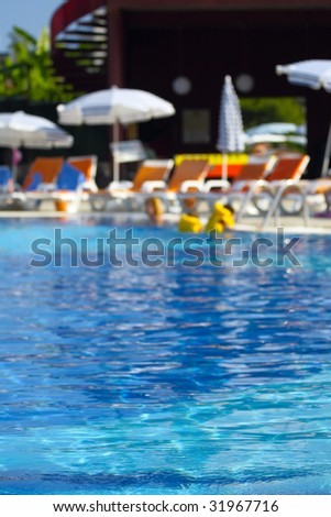 Resort pool in sun day, blured background. Vertical composition.