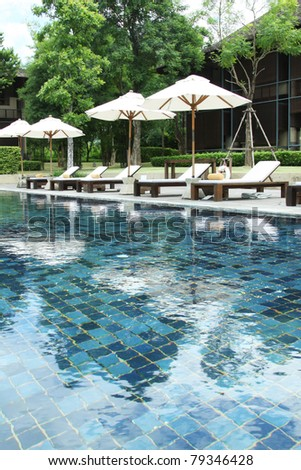 resort pool, Scenery of resort pool with sun beds and umbrellas. - stock photo