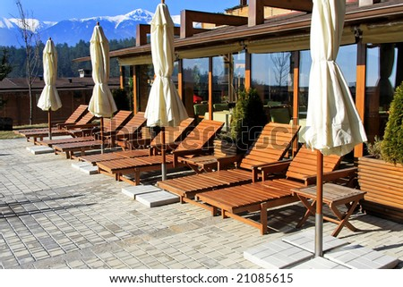 Resort terrace with swimming pool and sunny lounges - stock photo