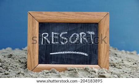 Resort written on a chalkboard at the beach - stock photo
