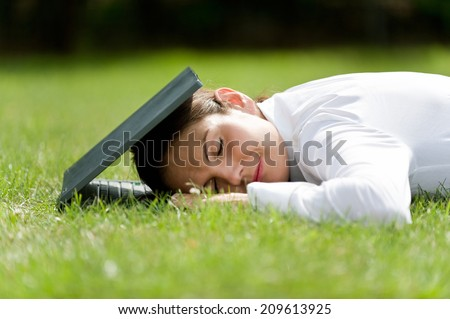 Rest after work, woman and computer, lying woman, lying woman with computer in the grass / Relaxation at work - stock photo