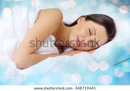 rest and comfort concept - beautiful woman sleeping in bed over blue lights background - stock photo