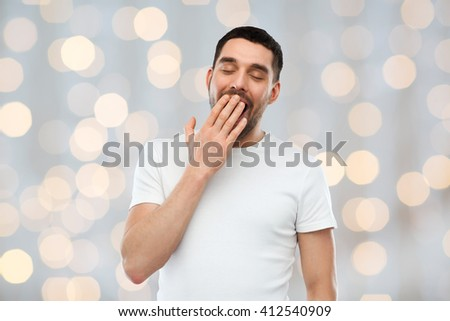rest, bedtime and people concept - tired yawning man over holidays lights background - stock photo