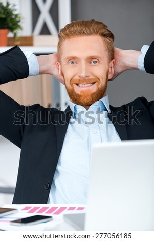 Rest for progress. Cheerful bearded businessman holding head in hands while sitting at his working place - stock photo