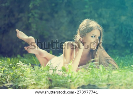 Rest in nature: Beautiful Woman lying on the grass - stock photo