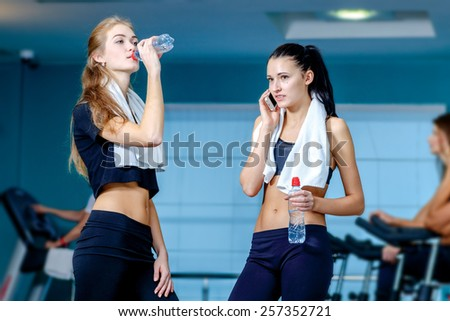 Rest in sports. Two friends are athletes in the gym and drinking water talking on a cell phone while their friends do sports and pedaling on a stationary bike - stock photo