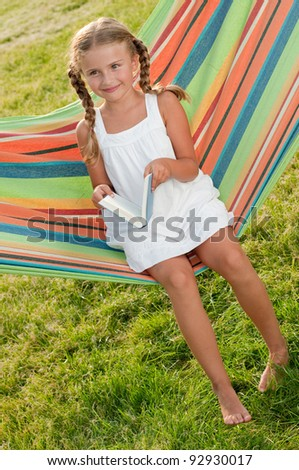 Rest in the garden  - Cute girl reading a book in colorful hammock