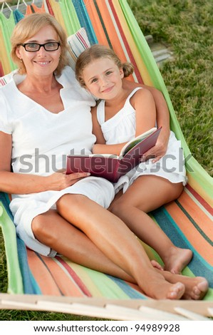 Rest in the garden, happy childhood - girl with mother reading a book in colorful hammock