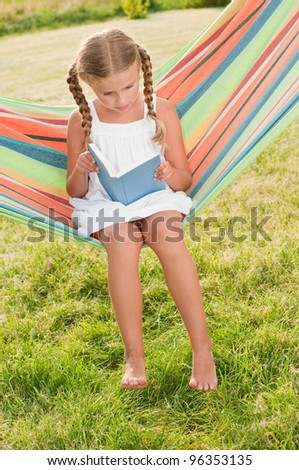 Rest in the garden, happy childhood - lovely girl reading a book in colorful hammock - stock photo