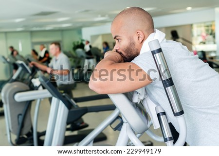 Rest in training. Portrait of a confident athlete to exercise in the cardio room. Two athletes engaged in the simulator gym - stock photo