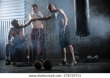 Rest three guys who have completed a complex crossfit workout - stock photo