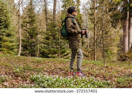 Rest while hiking. Traveling woman looking over the edge of a cliff with a forest in the background. - stock photo