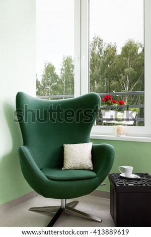 Rest zone. Comfortable lounge chair standing on the balcony of a luxury apartment - stock photo