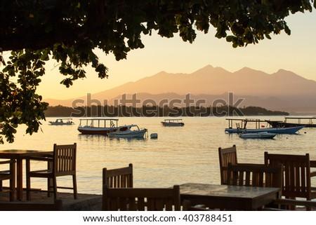 Restaurant and boats on the coast of Gili Travangan island with a sunrise view of Gunung Rinjani volcano on Lombok island, Indonesia. - stock photo