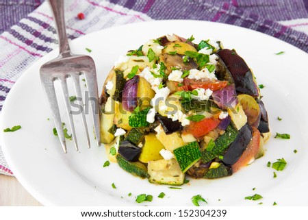 Restaurant appetizer of baked vegetables: eggplants, zucchini, potatoes, tomato and onion with feta cheese - stock photo