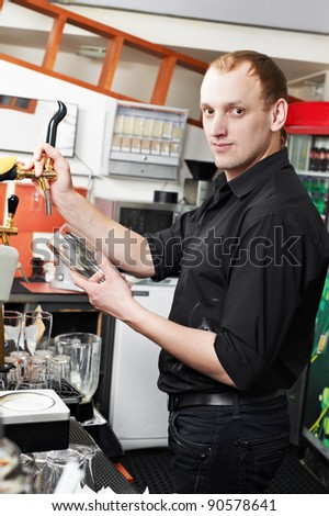 restaurant barman bartender pouring beer into glass at work place