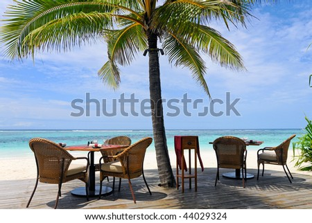 restaurant by the ocean under palm tree - stock photo