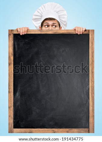 Restaurant chef hiding behind a big empty chalkboard for a business lunch menu with prices. - stock photo