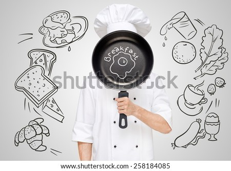 Restaurant chef hiding behind a frying pan with sketchy fried eggs for breakfast menu. - stock photo