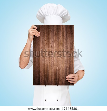 Restaurant chef hiding behind a wooden chopping board for a business lunch menu with prices. - stock photo