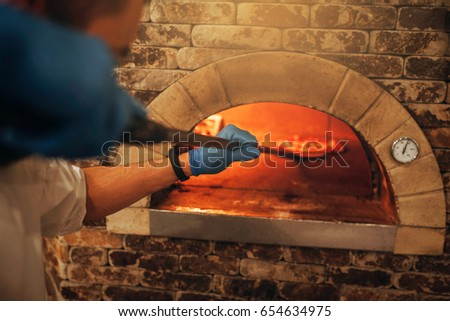 Restaurant chef takes pizza from oven in traditional restaurant