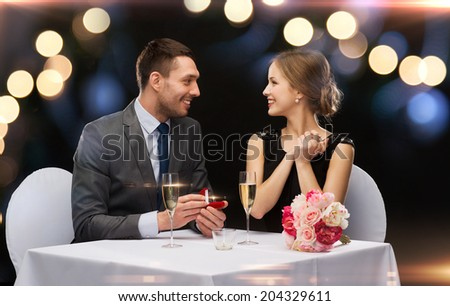 restaurant, couple and holiday concept - smiling man proposing to his girlfriend at restaurant - stock photo