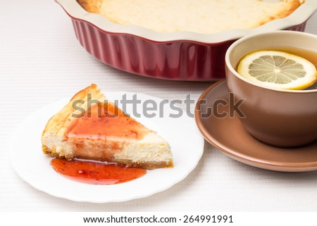 Restaurant dessert menu background. Homemade cheesecake with cup of tea with lemon - stock photo