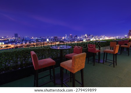Restaurant dining table and view of business building on terrace at twilight evening time