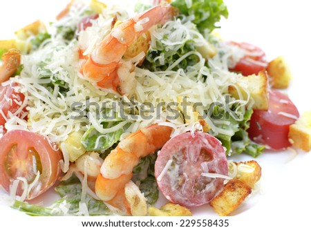 Restaurant dish, close up of tasty salad with shrimps, croutons, tomatoes, lettuce and cheese isolated on white - stock photo