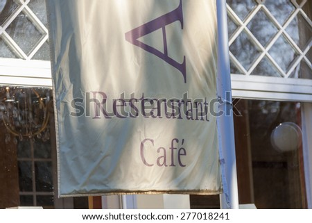 Restaurant flag or banner hanging from a flag pole outside a building