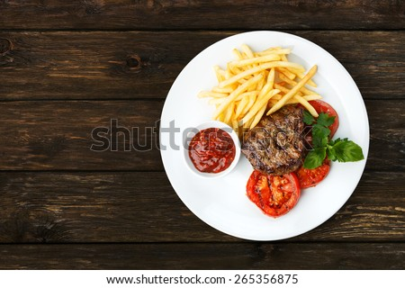 Restaurant food - beef grilled steak isolated at the wooden table, above view - stock photo