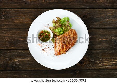 Restaurant food - chicken fillet grilled steak at wooden table - stock photo