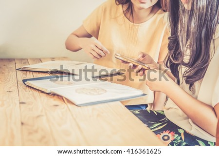 restaurant, food, eating and holiday concept - close up hand one of couple with mobile phone and menu choosing dishes at restaurant - stock photo