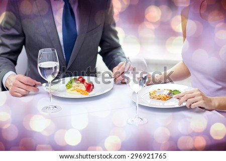 restaurant, food, people, date and holiday concept - close up of couple eating appetizers at restaurant over violet holidays lights background