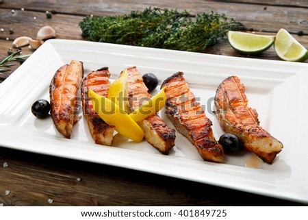 Restaurant food, salmon dish. Hot fish dish. Barbecue grilled fish dish. Restaurant food catering. Salmon barbecue grill roasted with lemon and olives. Grilled salmon served in restaurant closeup.  - stock photo