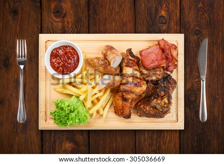 Restaurant food - served plate with grilled meat assortment with french fries served on wooden board  isolated at the white background - stock photo