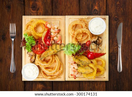 Restaurant food - served plate with roasted seafood with grilled vegetables assortment served on wooden board isolated at the white background - stock photo