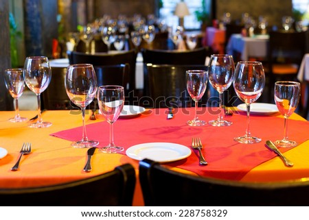 Restaurant hall. table appointments. Table with red and orange tablecloth, wine glasses, white plates and cutlery. (Soft focus.)
