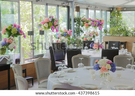 Restaurant hall with panoramic windows decorated with a lot of spring flowers