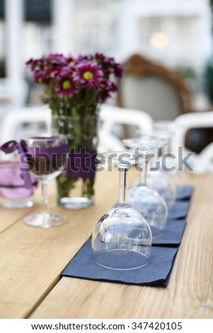 Restaurant interior details. Wineglasses and flower decoration. - stock photo