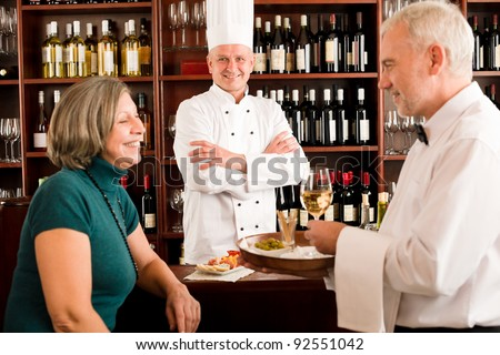 Restaurant manager smiling with staff at wine bar - stock photo