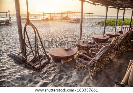 Restaurant on the beach with wooden chairs and tables at sunset in Goa, India - stock photo