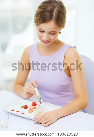 restaurant, people and holiday concept - smiling young woman eating dessert at restaurant