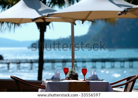 Restaurant places setting with romantic view to sea - stock photo