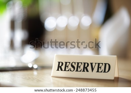 Restaurant reserved table sign with places setting and wine glasses - stock photo