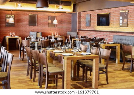 Restaurant room with wooden furniture and walls of red bricks - stock photo