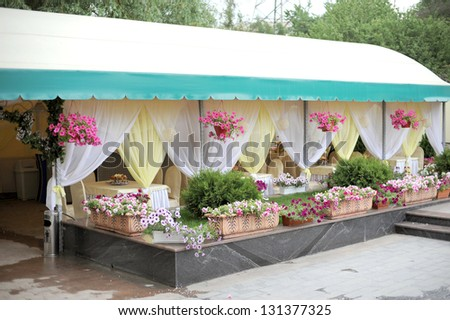 restaurant's porch decorated with flowerbeds - stock photo