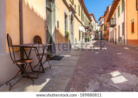 Restaurant's table with two chairs on paved narrow street between colorful houses in Alba, Italy. - stock photo